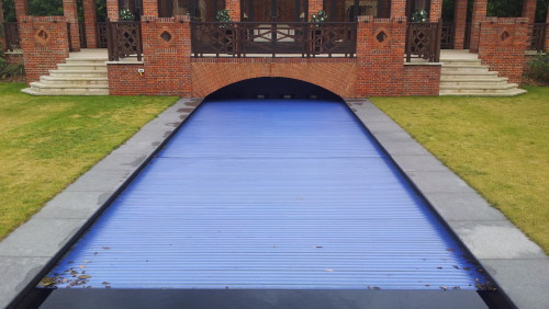 Outdoor Black mosaic pool with automatic slatted cover