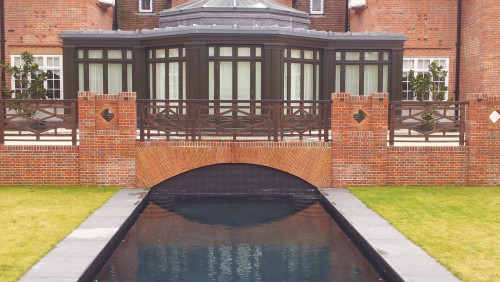 Outdoor pool in Black mosaic with a Basalt Decking